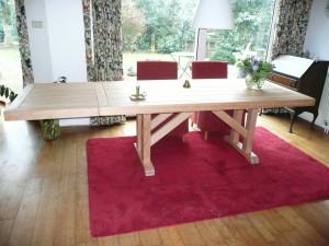 Eettafel met verlengstukken gemaakt van houten balken.